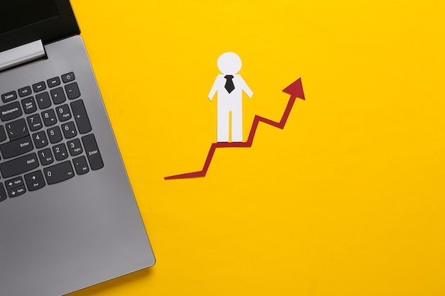 Laptop, paper business man on growth arrow. yellow. symbol of financial and social success, stairway to progress