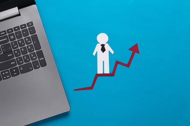 Ноутбук, бумажный деловой человек на стрелке роста. синий. символ финансового и социального успеха, лестница к прогрессу