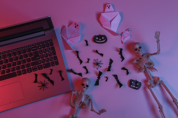 Laptop and paper-cut halloween decor in pink blue gradient neon light. top view. flat lay