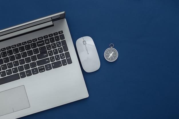 古典的な青い背景の上のラップトップ、pcマウスとコンパス。オンラインビジネスまたは旅行。上面図