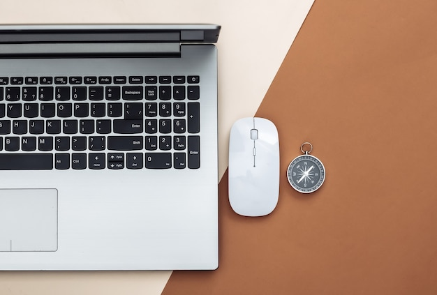 Laptop, pc mouse and compass on beige brown background. online business or travel. top view