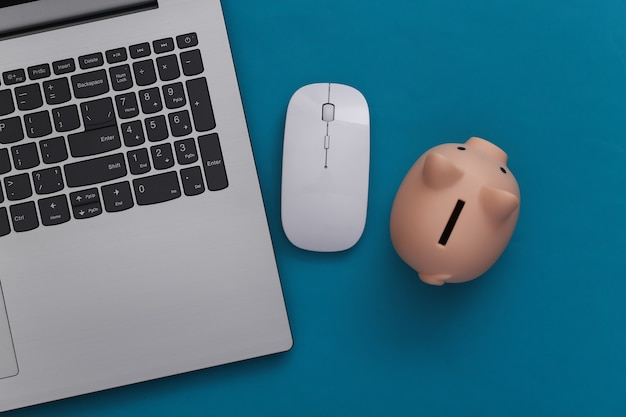 Laptop, pc mouse with piggy bank on blue background. internet payment. online business. top view. minimalism