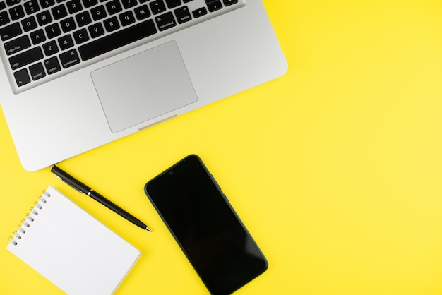 ノートパソコン、ペン、メモ帳プランナー、黄色の背景にスマートフォン。