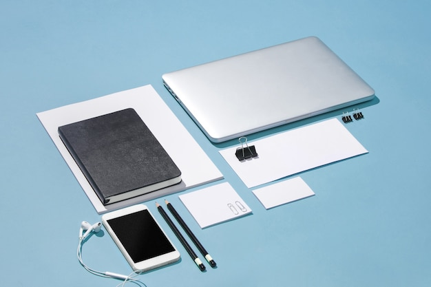 Laptop, pens, phone, note with blank screen on table