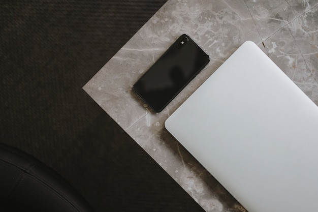 Laptop and a phone on a marble table