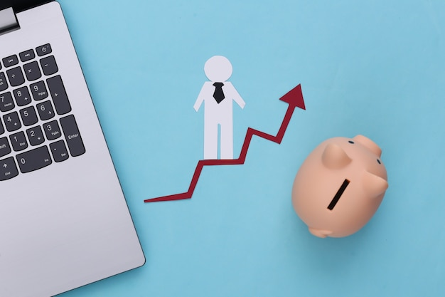 Laptop, piggy bank and paper man on growth arrow