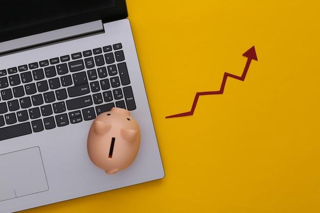 노트북, 노란색에 빨간색 성장 화살표와 함께 돼지 저금통. 올라가는 화살표 그래프