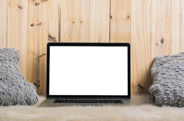 Laptop and pillow on soft fur against wooden background