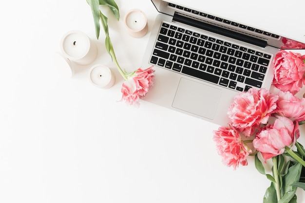 ノートパソコン、ピンクの牡丹のチューリップの花、白いテーブルの上のキャンドル。フラットレイ、上面図