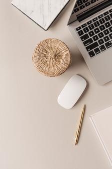 Ноутбук, шкатулка из ротанга, канцелярские товары на бежевом столе. плоская планировка, вид сверху