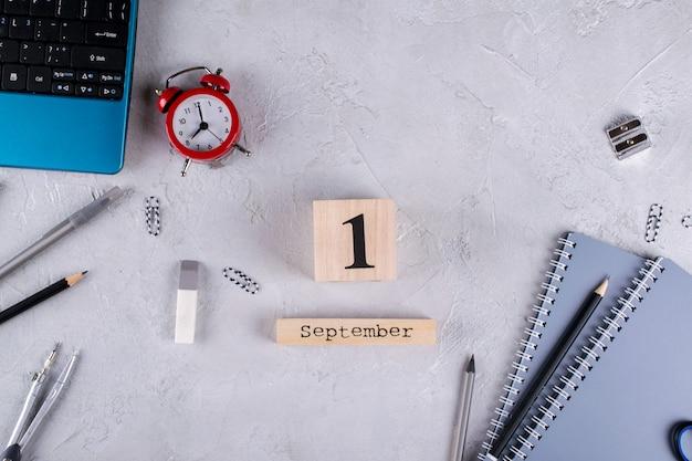 Ноутбук, красный будильник и принадлежности, деревянный календарь