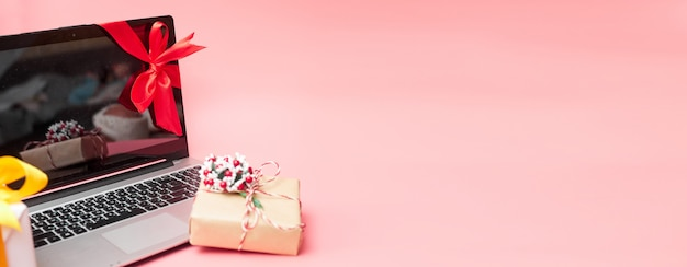 Laptop in a red ribbon with gifts, on a pink background, banner, copy space