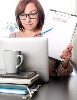 Ноутбук резюме держит женщину среднего возраста 50 плюс рабочее место пустое резюме приложение
