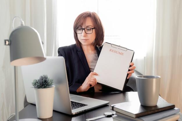 여자 중년 50 플러스 직장 빈 이력서 시트 응용 프로그램을 들고 노트북 이력서