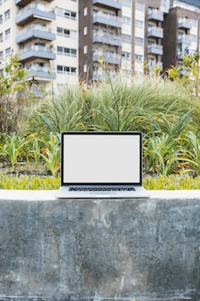 Laptop on retaining wall in front of apartment