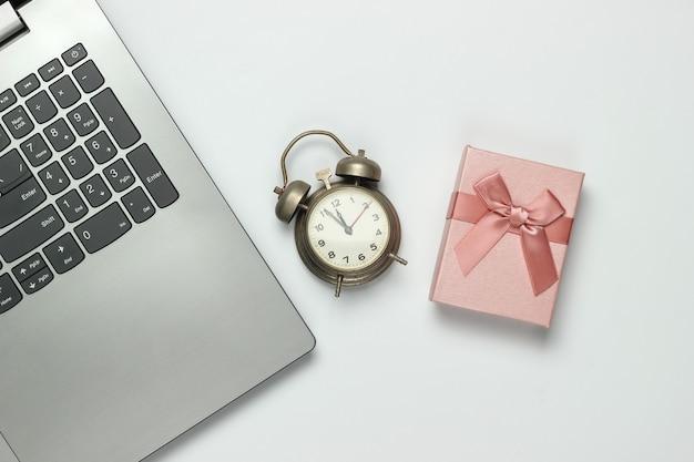 ノートパソコン、レトロな目覚まし時計、白い背景に弓が付いたギフトボックス。午前11時55分。新年、クリスマスのコンセプト。上面図