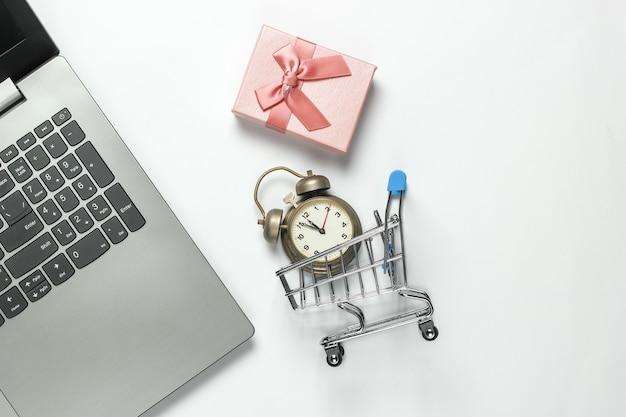 노트북, 복고풍 알람 시계, 쇼핑 트롤리, 흰색 바탕에 활과 선물 상자. 오전 11:55 새 해, 크리스마스 개념입니다. 휴일 온라인 쇼핑. 평면도