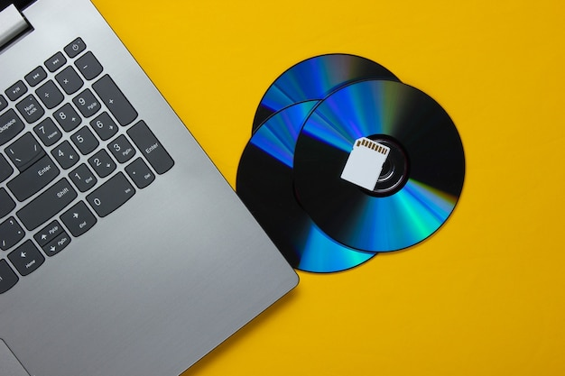 Laptop,  sd memory card, cd drives on yellow paper with geometric shapes