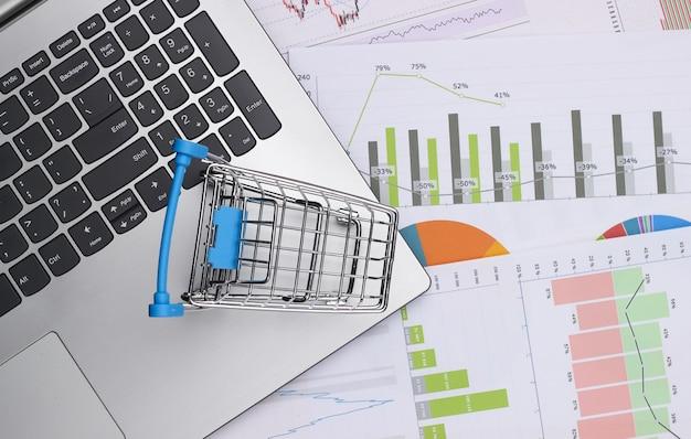 Ноутбук, тележка для покупок с графиками и диаграммами. бизнес-план, финансовая аналитика, статистика. вид сверху
