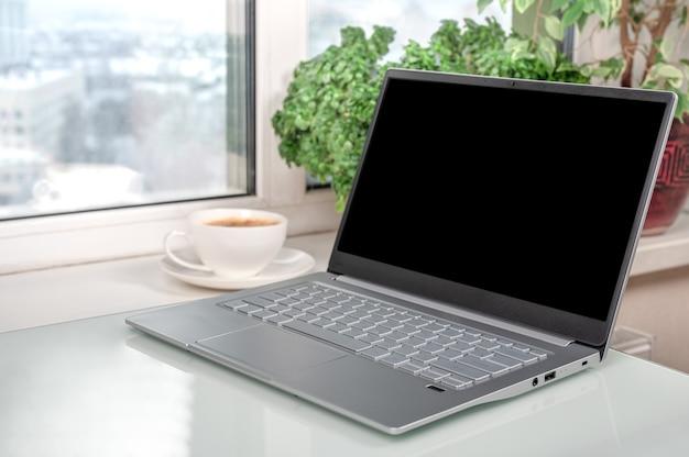 コーヒーショップやホームオフィスで空白の画面を表示しているラップトップ。ホームオフィススペースのテーブルに空白の画面があるノートブック。