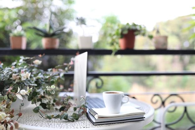 Вид сбоку ноутбука белый макет и чашка кофе с ноутбуками на белом столе на открытом воздухе