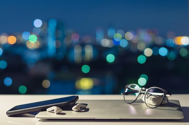 Ноутбук, смартфон и наушники выключаются, положить на стол с красочными городскими огнями боке