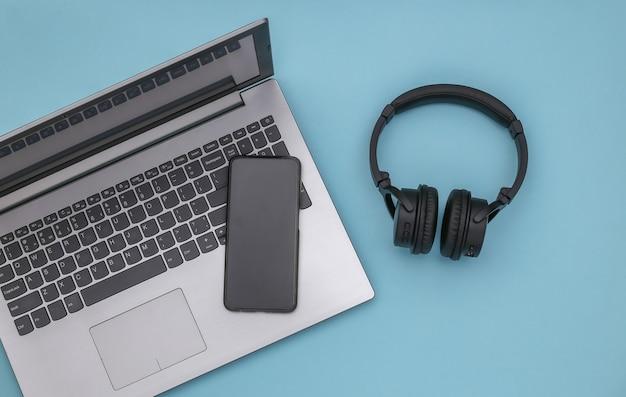 Ноутбук, смартфон и беспроводные стереонаушники на синем фоне. вид сверху. плоская планировка
