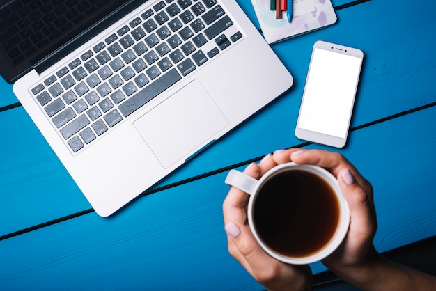 Laptop and smartphone on blue desk with coffee