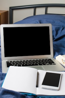 Laptop and smartphone, coffee cup and notebook on the bed in morning time. mock up.