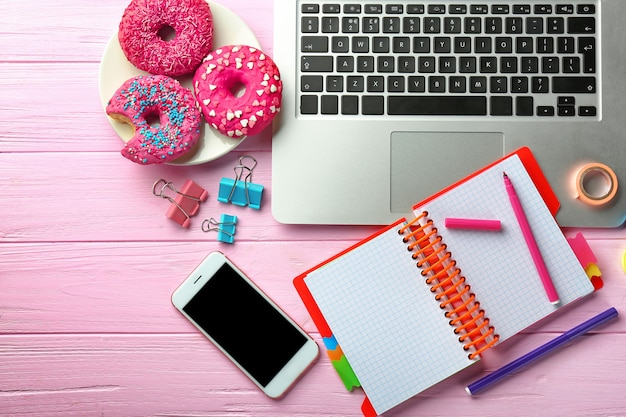 Laptop, smartphone, doughnuts and stationery on table, flat lay. workplace composition