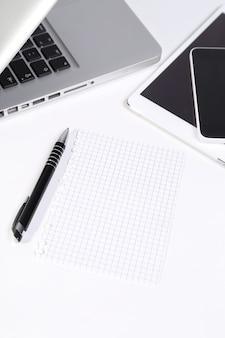 ノートパソコン、スマートフォン、タブレット、テーブルの上のペン