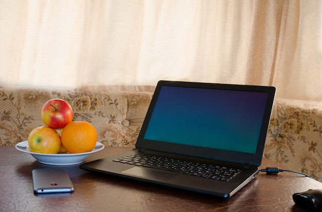 Laptop on a table in a cozy kitchen with a plate of fruit, a smartphone. break