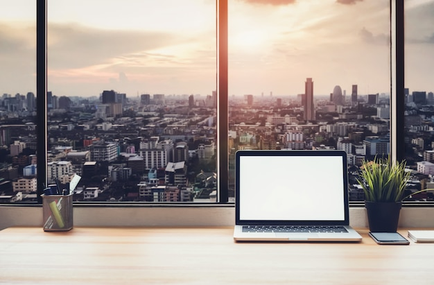 Laptop on table in office room on window city background