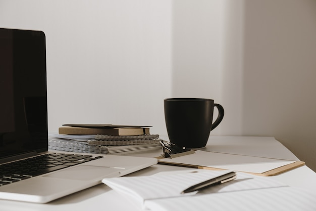 Laptop on table with coffee cup, paper sheet against white wall