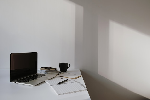 Laptop on table with coffee cup, paper sheet against white wall.