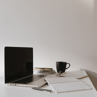 Laptop on table with coffee cup, paper sheet against white wall Premium Photo
