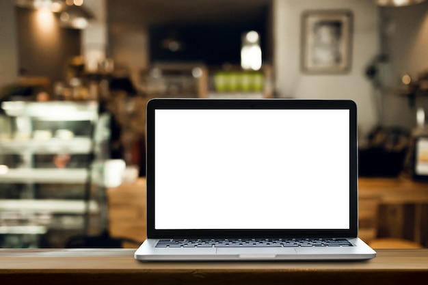Laptop on the table with coffee shop background.