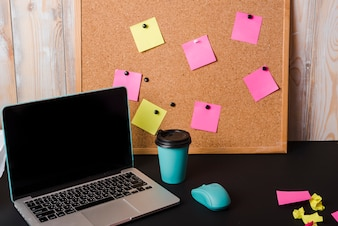 Laptop; takeaway coffee cup; mouse and corkboard with adhesive notes on black desk