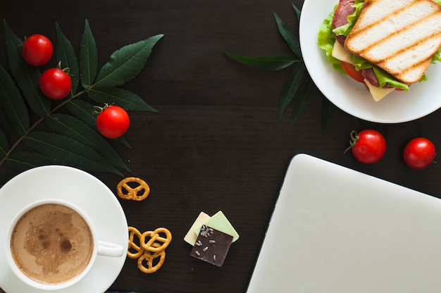 Laptop; tomatoes; sandwich; chocolate pieces; pretzels and coffee cup on black background