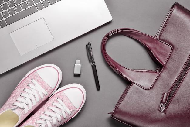 Ноутбук, флешка и модные женские аксессуары на серой поверхности