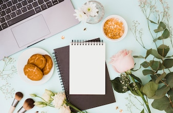 Laptop; vase; bouquet; makeup brush; cookies and golden pushpin on blue background