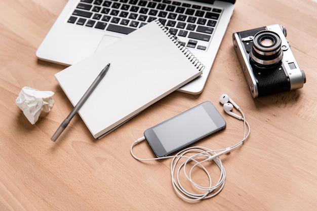 Ноутбук, старинный фотоаппарат, мобильный телефон с наушниками и блокнот с ручкой, лежащий на деревянном столе