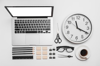 Laptop; wall clock; cup of coffee and office stationery on white backdrop