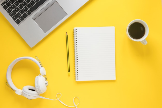 Laptop; white headphone; coffee cup; pencil and spiral notepad on yellow backdrop