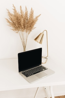 Laptop on white table with golden lamp and pampas grass