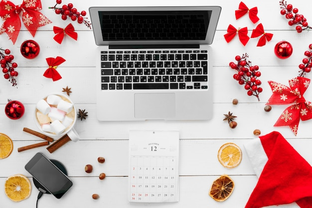 Laptop on white wooden desk surrounded with red christmas decorations, top view