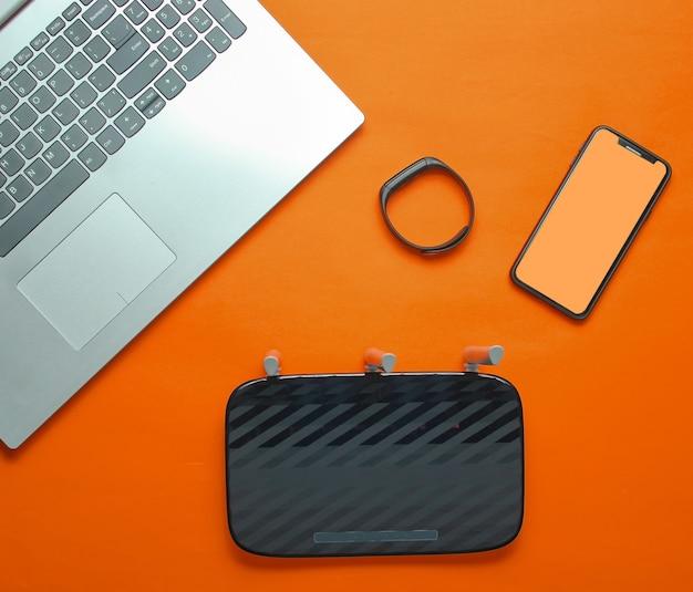 Laptop, wi-fi router, smartphone, smart tracker on orange background