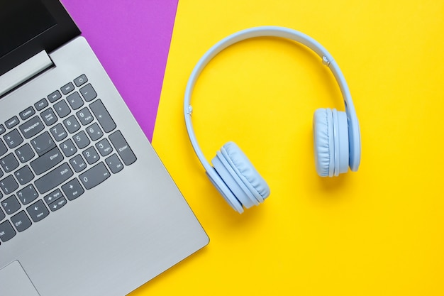 Ноутбук, беспроводные наушники на пурпурно-желтом фоне.