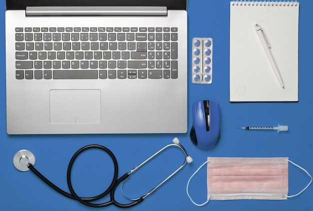 Laptop, wireless mouse, notebook, stethoscope, pills on blue background