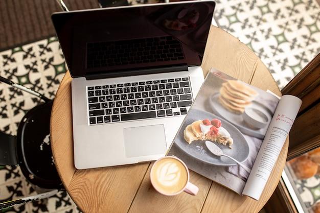一杯のコーヒーとラップトップ。在宅勤務。コーヒーショップで働く。自分の時間